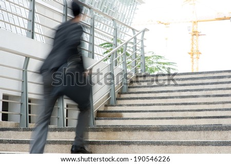 Businessman in hurry. Motion blurred people over office building. - stock photo