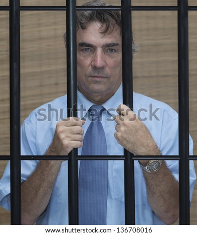 businessman in jail behind bars - stock photo