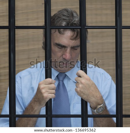 businessman in jail behind bars for drunk driving - stock photo