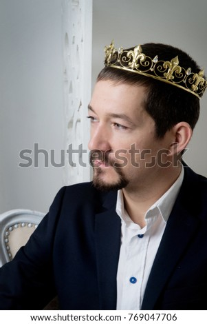 Businessman in modern costume, suit sitting in chair with golden crown