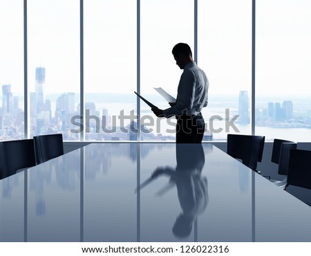 businessman in office and city in window - stock photo