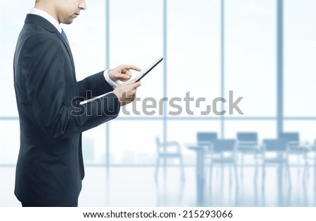 businessman in office holding touch pad in hand - stock photo