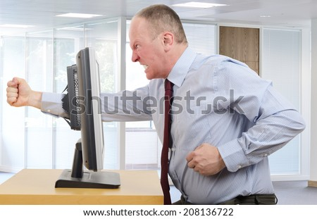 Businessman in office in a rage with a computer screen - stock photo