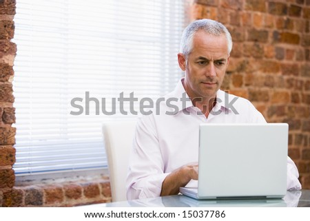Businessman in office looking at laptop - stock photo