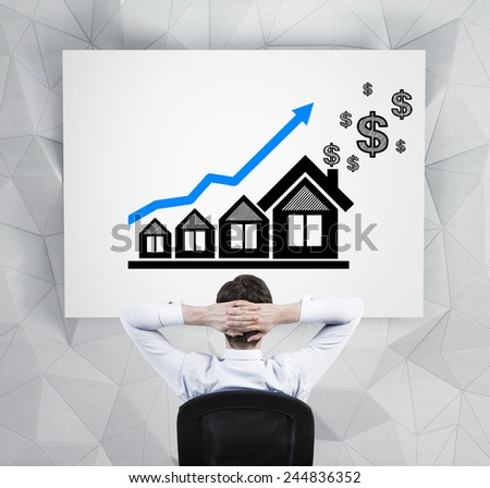 businessman in office looking on drawing blue chart  and house