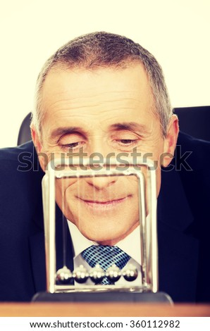 Businessman in office playing with newton balls - stock photo