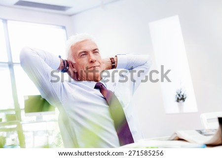 Businessman in office relaxing leaning back on chair - stock photo