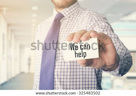 businessman in office showing card with text: We can help  - stock photo
