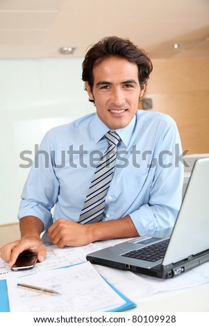 Businessman in office sitting at his desk - stock photo