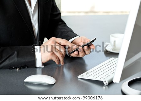 Businessman in office talking on the touch tablet phone gadget. - stock photo