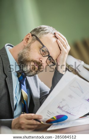 businessman in office thinks holding head hand. in the office - stock photo