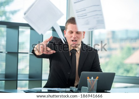 Businessman in office throwing papers at camera