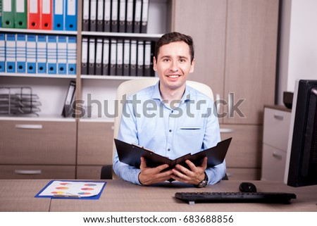 Businessman in office with a folder in hands. Business and investment