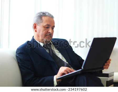 businessman in office with laptop sits and works