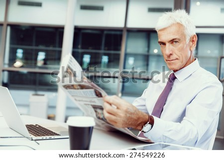 Businessman in office with newspaper - stock photo