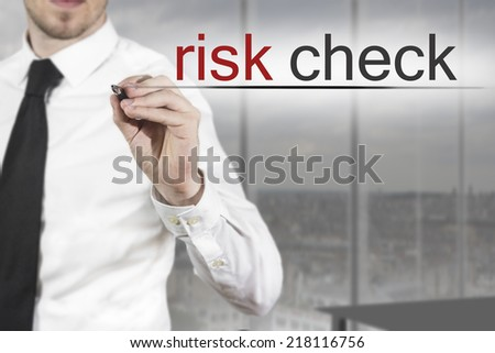 businessman in office writing risk check in the air - stock photo