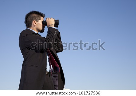 Businessman in outdoor looking though binoculars - stock photo