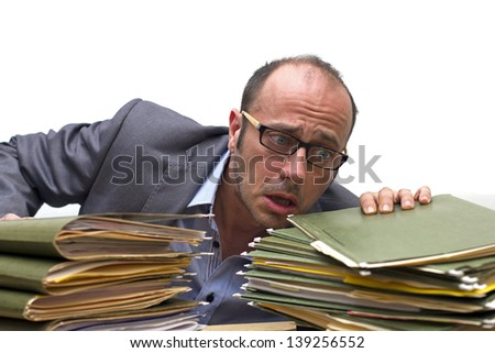 businessman in panic in front of piles of folders - stock photo