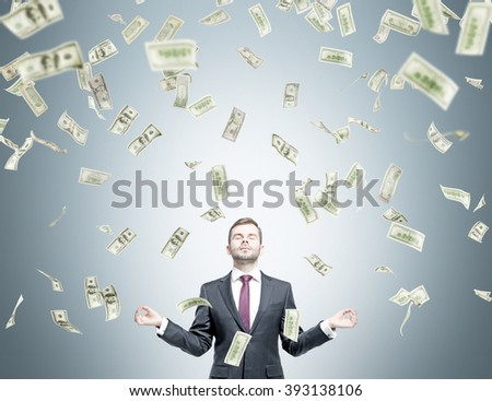 Businessman in posture of meditation, dollars falling from above. Grey background. Concept of getting money. - stock photo