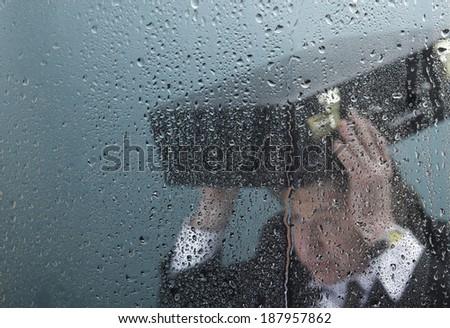 Businessman in rain behind wet window - stock photo