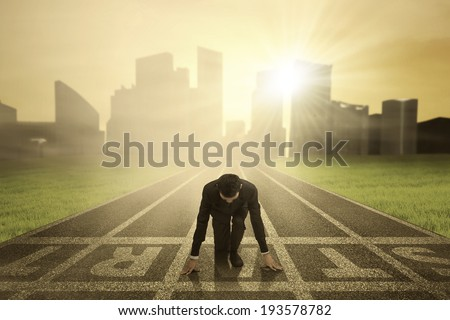 Businessman in ready position to race on the track - stock photo