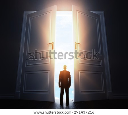 businessman in room with big open door - stock photo