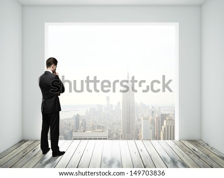 businessman in room with big window - stock photo