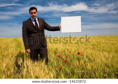 businessman in rural field holding a blank board - stock photo