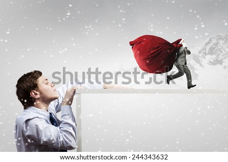 Businessman in Santa hat running with bag on back - stock photo