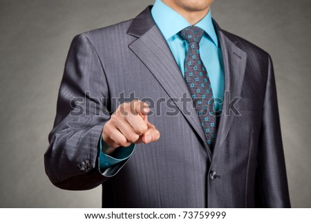 businessman in suit and tie pointing the finger in front of himself - stock photo