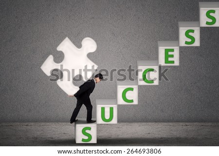 Businessman in suit carry a piece of puzzle on success stairs - stock photo