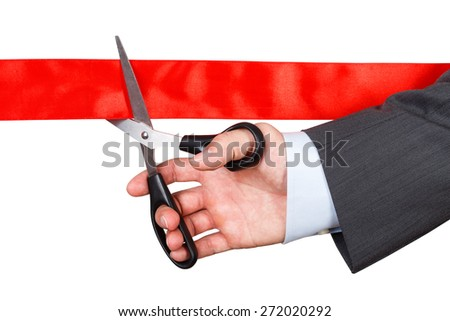 Businessman in suit cutting red ribbon with pair of scissors isolated on white background. Grand opening concept. Traditional public festive ceremony. - stock photo