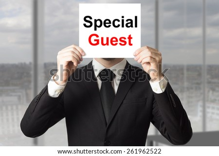 businessman in suit hiding face behind sign special guest - stock photo