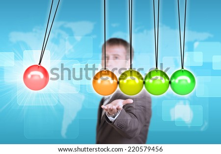 Businessman in suit hold Newtons cradle. World map and rectangles as backdrop - stock photo