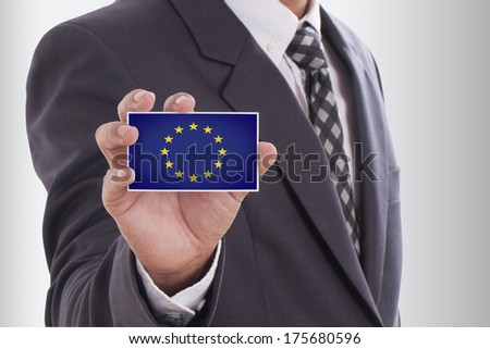 Businessman in suit holding a business card with a European Union Flag - stock photo