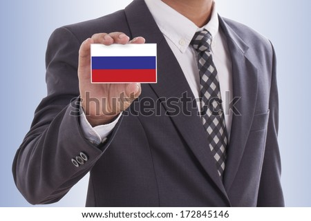 Businessman in suit holding a business card with a Russia Flag  - stock photo