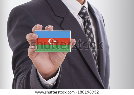 Businessman in suit holding a business card with Azerbaijan Flag  - stock photo