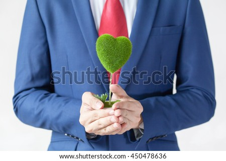 Businessman in suit holding a green heart shape - white background - indicates eco-friendly , social and environmental responsibility business concept - stock photo