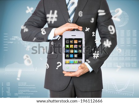Businessman in suit holding big smart phone. Graphs and figures on background - stock photo