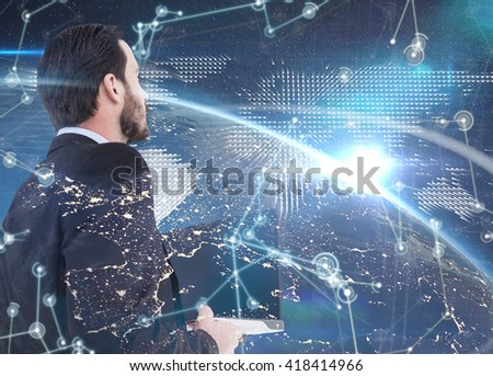 Businessman in suit holding laptop against hologram background - stock photo