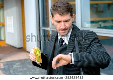 businessman in suit in front of city- background is eating and looking for time - stock photo