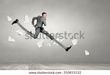 Businessman in suit jumping with big springs on feet - stock photo
