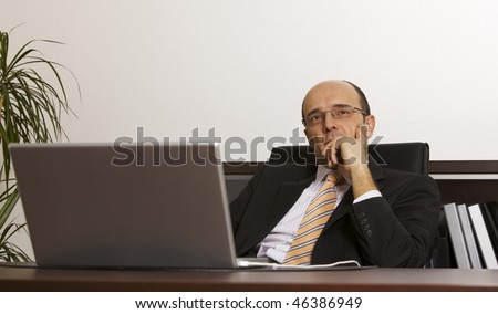 Businessman in suit leaning back in chair pondering over business strategies and concepts at desk with laptop in office - stock photo