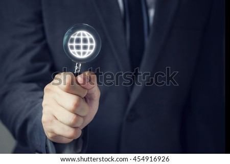 Businessman in suit looking for virtual world using a small magnifier - stock photo