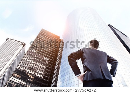 businessman in suit looking on big skyscraper - stock photo