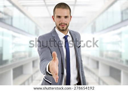 businessman in suit offering to shake the hand at the office - stock photo