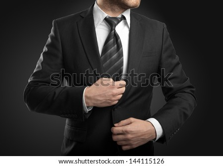 businessman in suit  on black background - stock photo