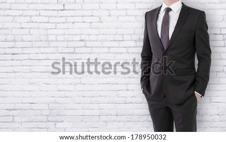 businessman in suit on brick wall background with place for your text