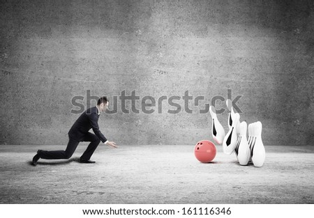 businessman in suit playing bowling in concrete room - stock photo