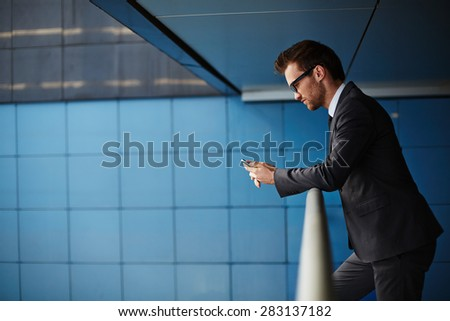 Businessman in suit reading or writing sms while standing by railings in office building